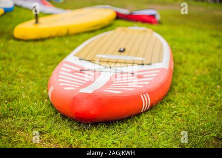 SUP boards lying on the grass by the river, lake or sea - Stock Photo