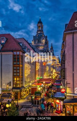 Colorful illuminated christmas market in the street Münzgasse, the rebuilt Church of our Lady behind - Stock Photo