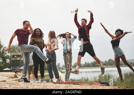 Let's go crazy. Group of people have picnic on the beach. Friends have fun at weekend time