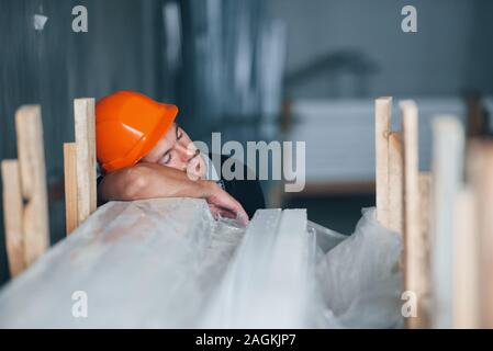 Sleeping on a job. Taking a break. Industrial worker indoors in factory. Young technician with orange hard hat