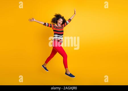 Discounts i come. Full size profile side photo of crazy funky afro american girl jump run want spring weekend bargains wear striped shirt red pants - Stock Photo
