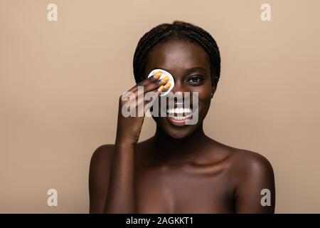 Close up portrait of an attractive african american woman removing makeup with sponge