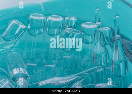 Glass medical ampoule vial for injection. Medicine is liquid sodium chloride with of aqueous solution in ampulla. Close up. Bottles ampule multicolor. - Stock Photo