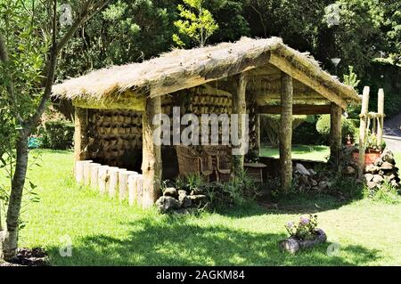 Wooden hut with wooden chairs under the straw roof in the countryside (Madeira, Portugal, Europe) - Stock Photo