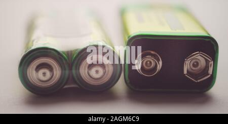 Two different types of batteries on the table close-up. - Stock Photo