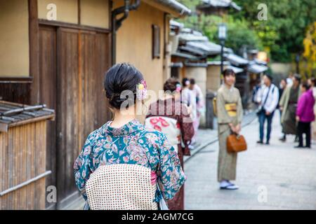 KYOTO, JAPAN -17th  November 2019:Tourists dressed in traditional kimono visit Ninezaka and Sannenzaka iconic streets  lined with old wooden buildings - Stock Photo