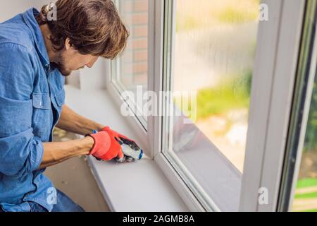 Man in a blue shirt does window installation - Stock Photo