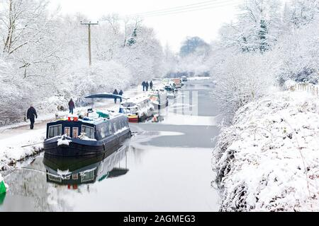 BATH, UK - 19 JAN : Walkers pass moored boats on the Kennet and Avon canal in the snow on 19th Jan 2013. The boats stay moored throughout the winter - Stock Photo