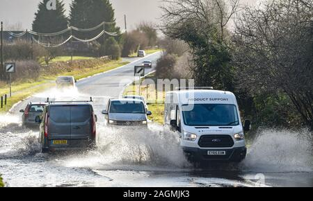 Brighton UK 20th December 2019 - Traffic drives through floodwater on the B2118 in the village of Albourne just north of Brighton in Sussex . The M23 has been closed in both directions after overnight flooding and heavy rain caused havoc with commuters and Christmas holiday travellers . Credit: Simon Dack / Alamy Live News - Stock Photo