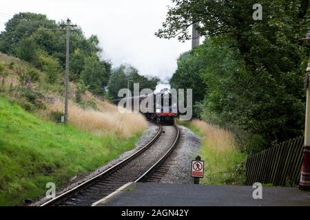 British Railways former standard 4-6-0 steam locomotive 75078 approaches Haworth Station on the Keighley & Worth Valley  heritage preservation line - Stock Photo