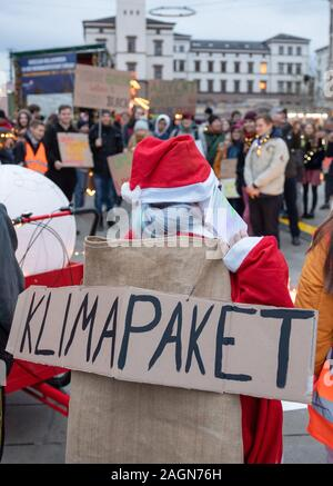 Erfurt, Germany. 20th Dec, 2019. A Christmassy dressed participant of a Fridays for Future 'light demo' under the motto 'A light in the darkness - climate justice now!' carries a poster with the words 'climate package' on his back. With this campaign, the students and participants are also looking back on a year of Fridays for Future Erfurt. Credit: Michael Reichel/dpa-Zentralbild/dpa/Alamy Live News - Stock Photo