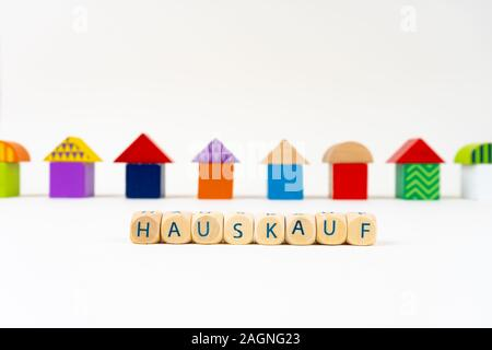 Wooden block with letters saying 'Hauskauf' (German for buying real estate) in front of colorful toy houses - Stock Photo