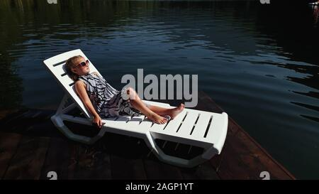 Kid girl lie on a sunbed in sunglasses and a boho silk shawl. Child rest on a flood wood underwater pier. The pavement is covered with water in lake. - Stock Photo
