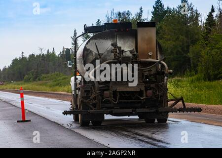 An industrial construction vehicle is seen covered in dirt and muck from the back, at work on the roadside during construction and upgrade of highway - Stock Photo