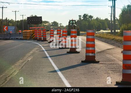 Temporary road cones and lane markings create leading lines as construction and resurfacing work begin on a main carriageway causing travel disruption - Stock Photo
