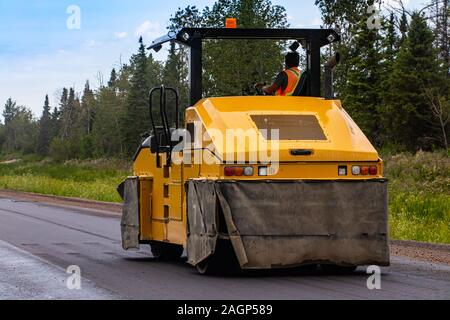 A close up shot of an industrial pneumatic ride on road roller, used to flatten and compact the asphalt surfacing of a highway during roadworks - Stock Photo