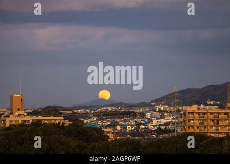 Full moon rises over distant mountain in small Japanese town at dusk - Stock Photo