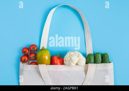 Zero waste concept. Vegetables in eco friendly reusable textile bag on blue background. Plastic free. Healthy fresh vegetarian food. Flat lay - Stock Photo