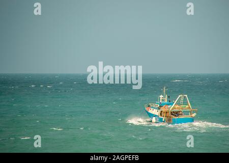 A small fishing boat heading out to sea to begin fishing. - Stock Photo