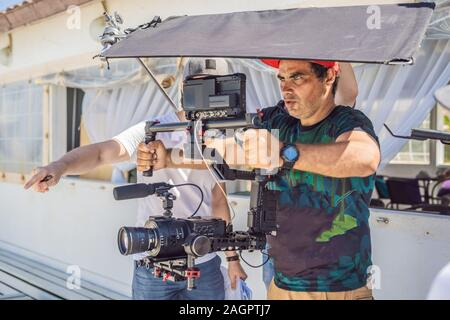 the production team on a commercial video shoot. Steadicam operator uses the 3-axis camera stabilizer and cinema-grade camera - Stock Photo