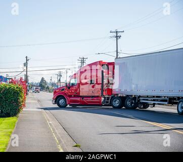 Big rig red powerful industrial grade professional semi truck tractor transporting dry van semi trailer with commercial cargo turning from city street - Stock Photo