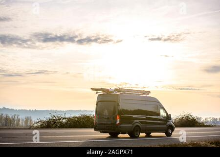 Dark comfortable compact commercial cargo mini van for local freight and deliveries and small business needs running with ladders on the roof on the r - Stock Photo