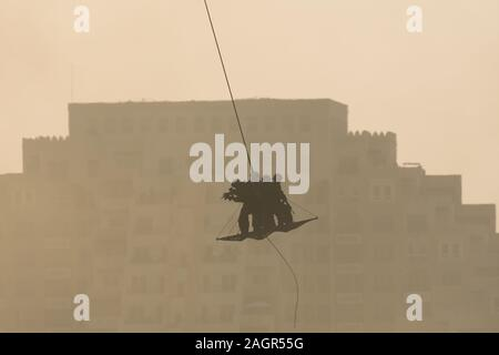 Military team in conflict rescuing people by helicopter. flying through the air on a rope attached to chopper in the smoke and haze in the MIddle East - Stock Photo