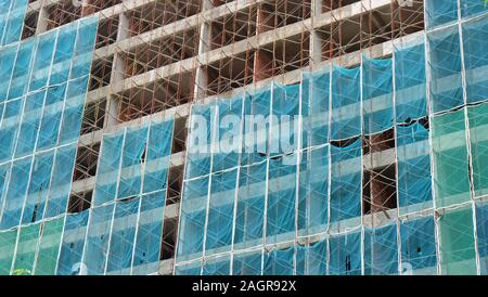 Tall building under construction, with metal construction rack and safety net covering the exterior. - Stock Photo