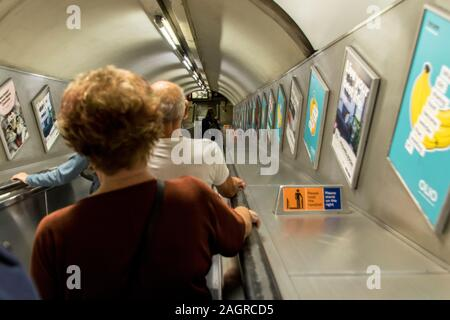 August 18, 2019 – London, United Kingdom. Passengers make their way through the tunnels and escalators of the London Underground system. - Stock Photo