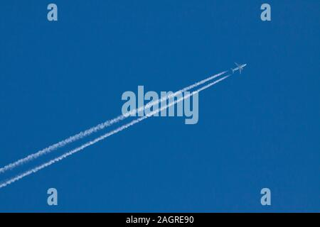Jet plane with contrails on clear blue sky background Bedfordshire England UK - Stock Photo