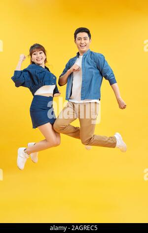 Full length body size view of nice attractive lovely cheerful cheery couple jumping up in air isolated over yellow background