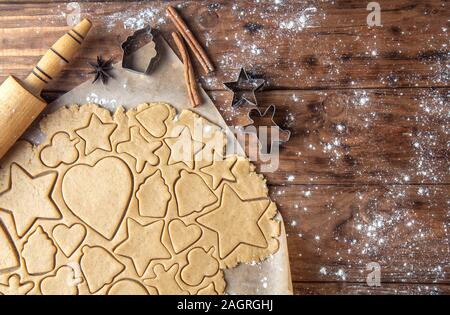 Cutting ginger biscuits in different shapes on a wooden background. Horizontal orientation, top view, place for text. - Stock Photo