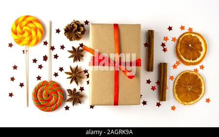 Creative concept food holiday celebration photo of christmas toys balls decoration with sweet candy lollipop and present box on white background. Stock Photo