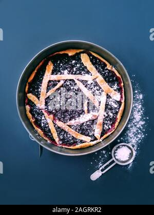 Round cake with black berries currant on a blue background, a recipe for sweet pastry from dough - Stock Photo