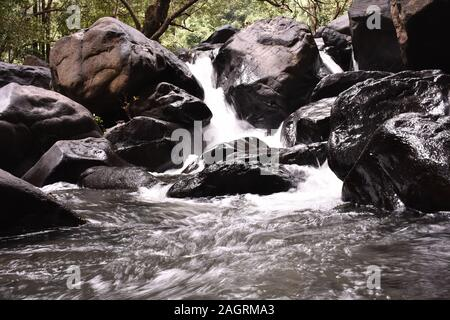 waterfall flowing through rocks with long exposure - Stock Photo