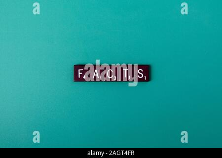 The word facts spelled out in wooden block letters on a blue green background - Stock Photo