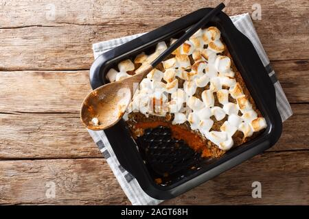 American sweet potato casserole with marshmallows close-up in a baking dish on the table. Horizontal top view from above - Stock Photo