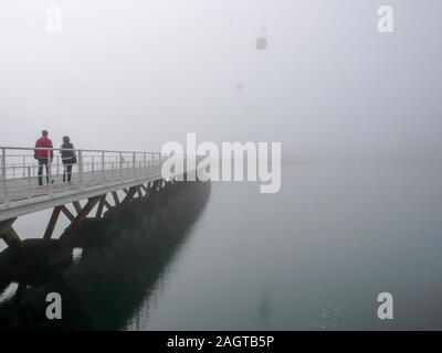 Lisbon, Portugal - 6. November, 2015: pedestrians crossing a long wooden bridge over calm water on a foggy and misty morning - Stock Photo