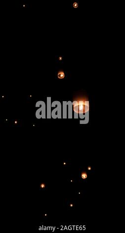 Released lanterns are flying in the sky at night in Thailand asia - Stock Photo