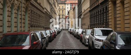 Many cars parked in line on both sides of old European city street - Stock Photo