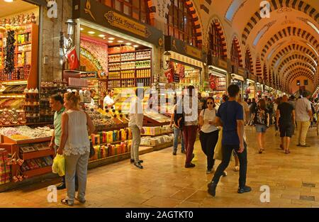 Istanbul, Turkey - September 6th 2019. Tourists walk past shops selling souvenirs, Turkish delight, spices, teas and dried fruit in the historic Egypt - Stock Photo