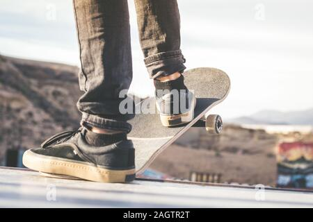 Close up view of teen's feet on a skateboard ready to start a ride over the half pipe. Skater starting jumps and tricks at the skate park. Let's go en