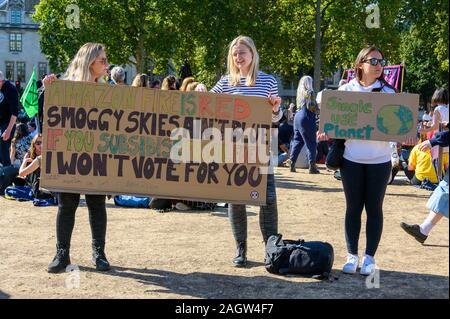 LONDON - SEPTEMBER 20, 2019: Female Climate Change protesters holding a home made protest sign in Parliament Square, London at an Extinction Rebellion - Stock Photo