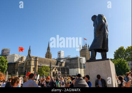 LONDON - SEPTEMBER 20, 2019: Statue of Winston Churchill overlooking an Extinction Rebellion protest in Parliament Square, London with The Houses of P - Stock Photo