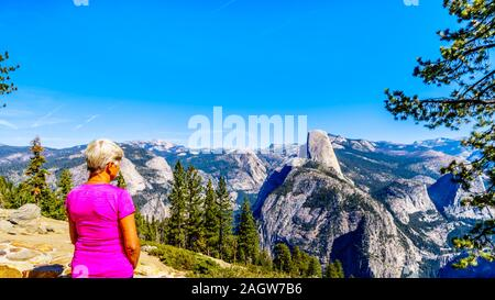 View from Glacier Point at the end of Glacier Point Road of the Sierra Nevada high country, with the famous Half Dome in the foreground in Yosemite,CA - Stock Photo