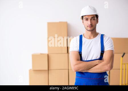 The young male professional mover doing home relocation - Stock Photo