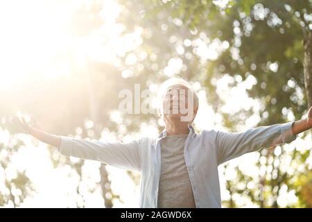 senior asian man enjoying fresh air walking with open arms outdoors in park