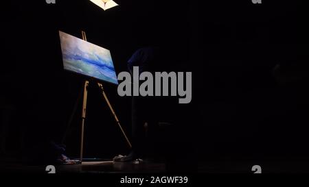 Artist copyist paint seascape with ship in ocean. Craftsman decorator draw as boat sail on blue sea. Black background. Wide angle shot. - Stock Photo