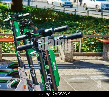 Frankfurt, Germany, October 2., 2019: Parked e-scooters for rent on the sidewalk in front of nenches and plants - Stock Photo
