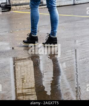 Reflection in water puddle, rainy day. - Stock Photo